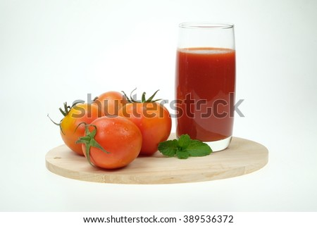 Glass of fresh tomato juice and tomatoes on a wooden cutting board