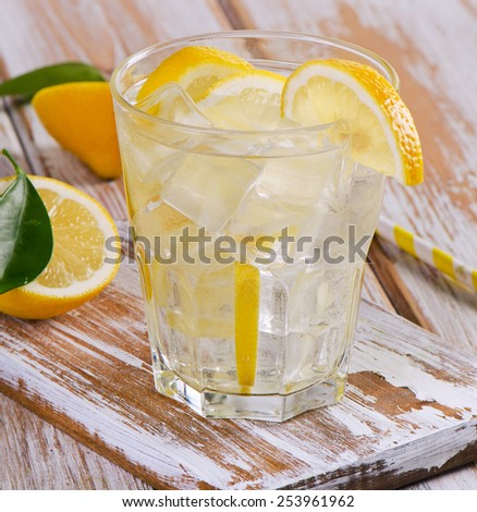 Glass of fresh water with a lemon. Selective focus - stock photo