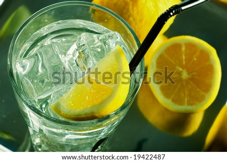 Glass of fresh water with cubes of ice and lemon - stock photo