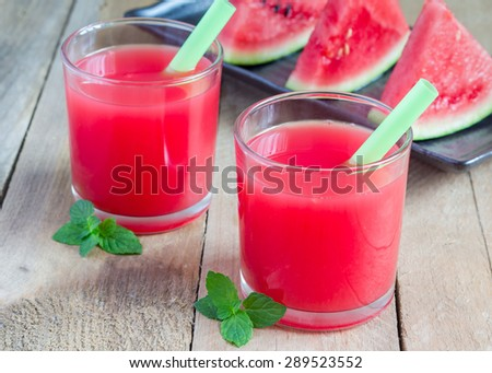 Glass of fresh watermelon juice on a wooden table - stock photo