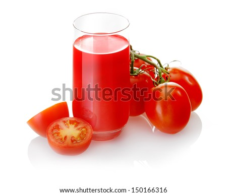Glass of freshly prepared healthy vegetarian tomato juice with halved and whole fresh grape tomatoes, some in a bunch on the vine - stock photo