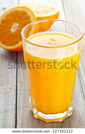 Glass of freshly pressed orange juice with sliced orange half on wooden table - stock photo