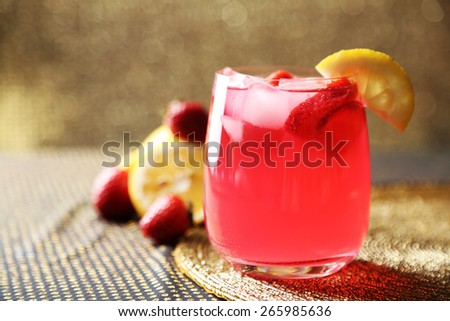 Glass of freshness lemonade with strawberries, on bright background - stock photo
