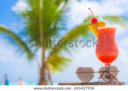 glass of fruit cocktail and heart shaped sunglasses on table near the beach - stock photo
