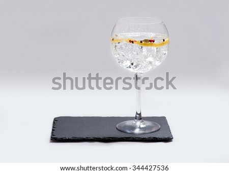 glass of gin and tonic on slate plate with white background - stock photo