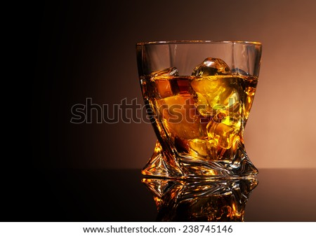 Glass of golden brandy on a brown background - stock photo