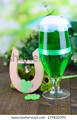 Glass of green beer and horseshoe for St Patricks day on wooden table close-up - stock photo