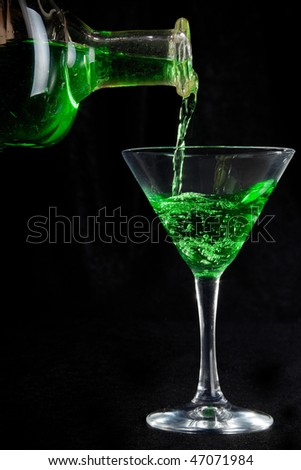 glass of green cocktails and bottle on black