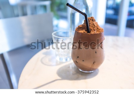Glass of iced chocolate and bottle of water and empty glass on marble table - stock photo