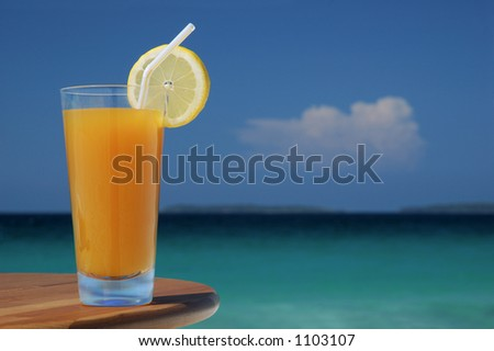 Glass of Juice with Lemon Twist and Straw Against Tropical Sea