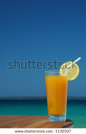 Glass of Juice with Lemon Twist and Straw Against Tropical Sea - stock photo