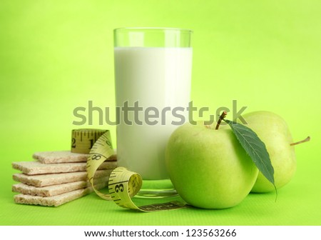 Glass of kefir, apple, crispbreads and measuring tape, on green background - stock photo