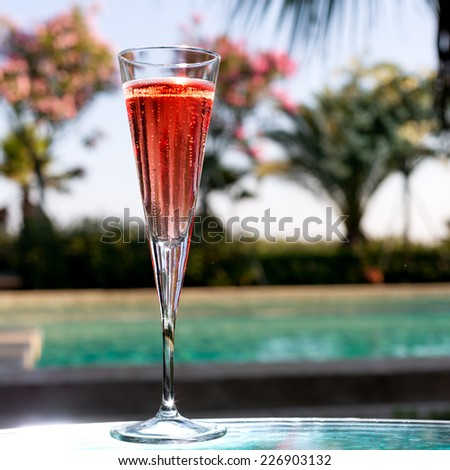 Glass of Kir Royal on the glass table in outdoor resort bar - stock photo