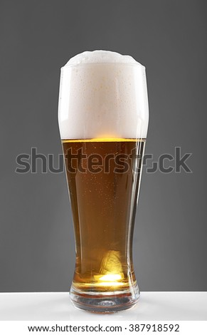 Glass of lager beer with thick froth on grey background