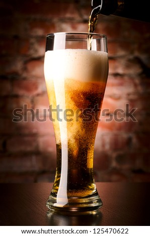 glass of lager on table against brick wall - stock photo