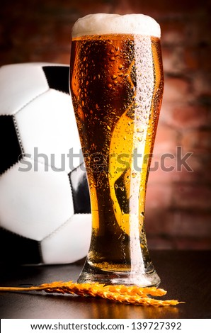 glass of lager on table with soccer ball against brick wall