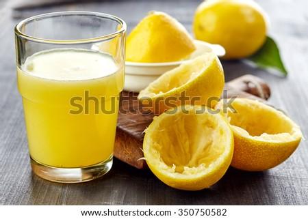 glass of lemon juice on wooden table - stock photo