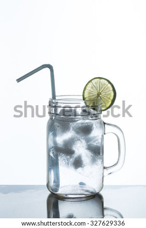 glass of lemonade and ice with slice of lime