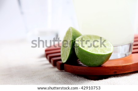 Glass of lemonade on wooden tray over black background - stock photo