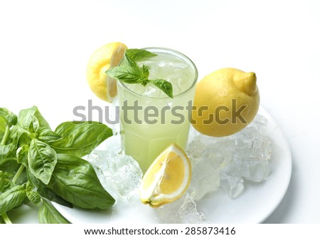 Glass of lemonade with basil leaves and lemons in ice cubes isolated on white background.