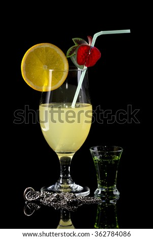 Glass of lemonade with bendie and orange slice and small glass of green drink on black mirror background with silver necklace and earrings with reflection - stock photo