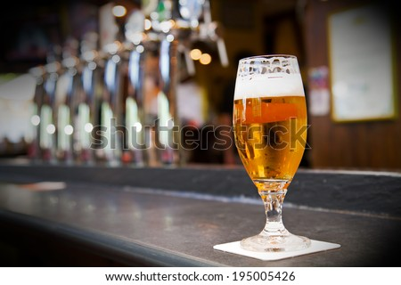 Glass of light beer on a pub - stock photo