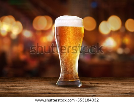 Glass of light beer on a pub with bokeh background.