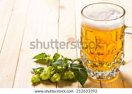Glass of light beer on a wooden table - stock photo