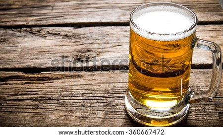 Glass of light beer on a wooden table. - stock photo