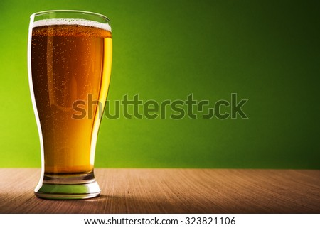 Glass of light beer on green background
