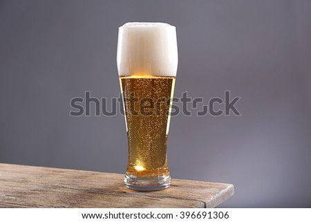 Glass of light beer on grey background - stock photo