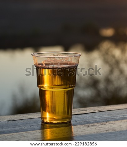 Glass of light beer on natural background, Plastic glass of beer in warm sunset light, glass of beer, glass of drink on summer, glass of beer on a table in open bar, cold beer plastic glass,light beer - stock photo