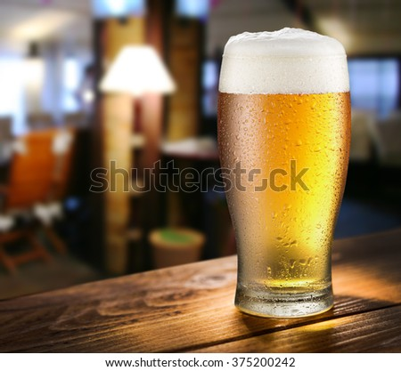 Glass of light beer on the glass bar counter. - stock photo