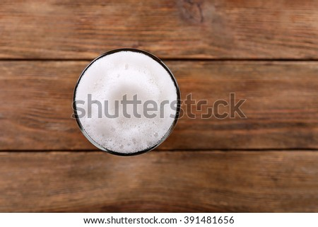 Glass of light beer with froth on wooden background