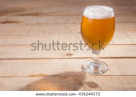Glass of light beer with tall white foam head on a wooden table - stock photo