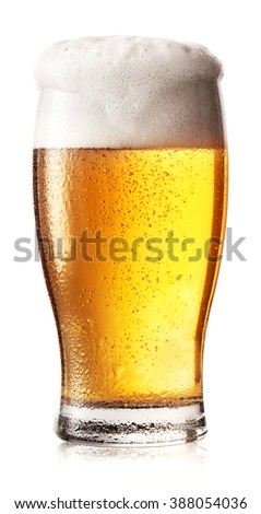 Glass of light beer with white foam and drops on the glass