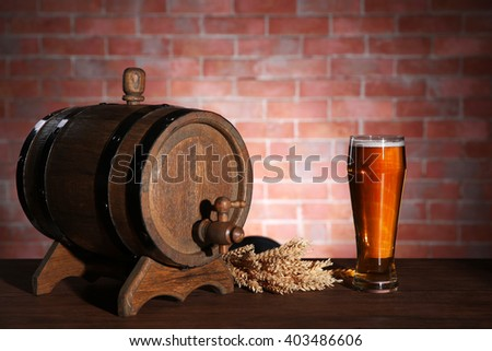 Glass of light beer with wooden barrel and barley ears on brick wall background