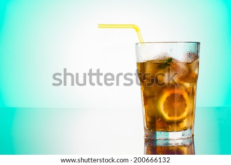 Glass of Long Island iced tea front mint green gradient background
