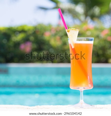 Glass of Mai Tai cocktail on the pool nosing at the tropical resort. Square, cocktail on right side - stock photo