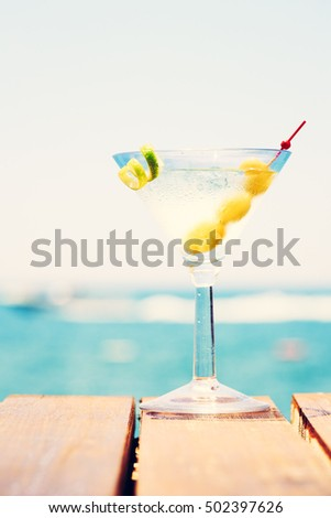 Glass of martini bianco at the wooden pier. Concept of summer vacation. Popular cocktail by the sea. Vacation background. Vertical, toned