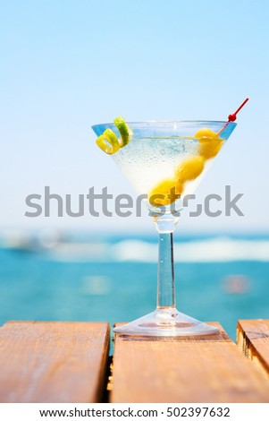 Glass of martini bianco at the wooden pier. Concept of summer vacation. Popular cocktail by the sea. Vacation background. Vertical