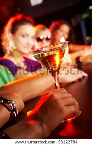 Glass of martini on background of row of smart teens in the nightclub - stock photo