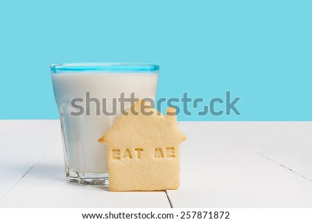 Glass of milk and biscuits with EAT ME sign  - stock photo