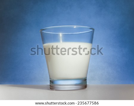 glass of milk and blue background in retro style - stock photo