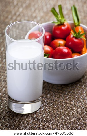 Glass of Milk and Bowl of Cherry Tomatoes and Mini Carrots on Patterned Placemat - stock photo