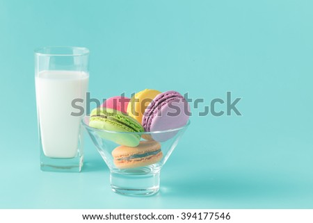 glass of milk and macaroon isolated on aquamarine background