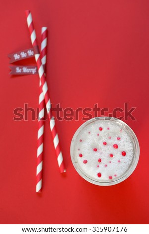 glass of milk and paper straws on red background - stock photo