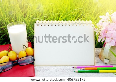 glass of milk, blank page calendar, yellow fruit,sunglasses, pencils and pink flower on white wood table with green grass nature lifestyle background - stock photo