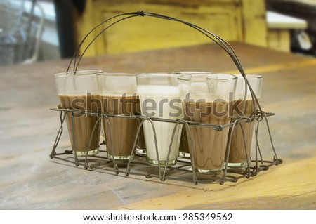 Glass of milk kept among chai in metal grid tray on a wooden surface - stock photo
