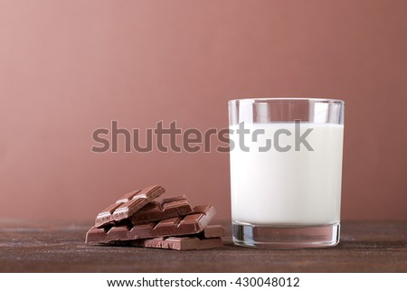 glass of milk on a chocolate background - stock photo